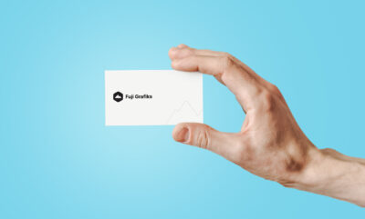 Free Person Holding Business Card PSD Mockup